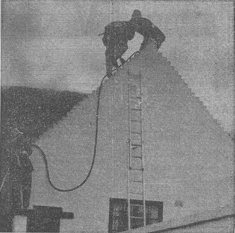 FIREMAN FALLS—Two firemen are seen on the gable-end before one of them, Sub Officer John Haydock, fell as brickwork gave way under him.