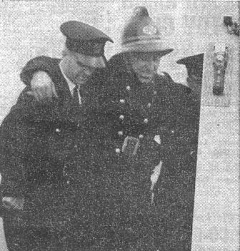 TO HOSPITAL.—Sub Officer Haydock is helped into the ambulance which was called for him after his fall.